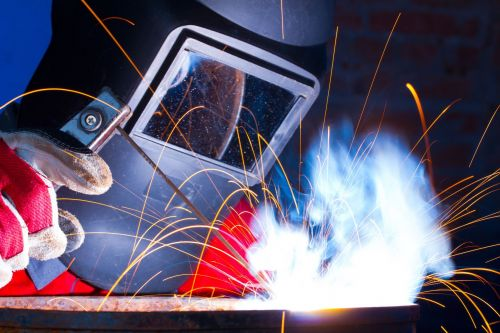 Welder working with metal and sparks flying.